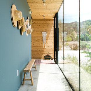 Modelo de recibidores y pasillos de estilo de casa de campo con paredes azules, suelo de cemento y suelo gris