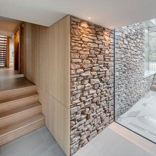 Modern inredning av en hall, med beige väggar, klinkergolv i terrakotta och vitt golv