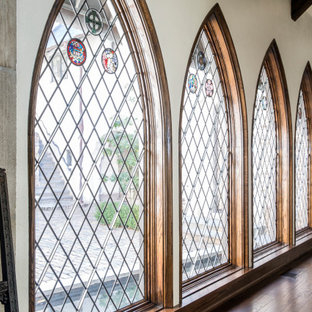 На фото: огромный коридор в классическом стиле с бежевыми стенами, темным паркетным полом, коричневым полом и балками на потолке с