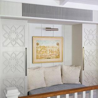 Idée de décoration pour un couloir ethnique avec un mur blanc, un sol en bois brun et un sol marron.