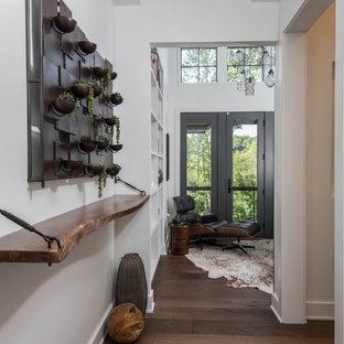 Photo of a mid-sized country hallway in Other with white walls and dark hardwood floors.