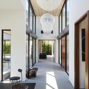 Aménagement d'un couloir moderne avec un mur blanc, béton au sol et un sol gris.