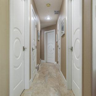 Cette image montre un grand couloir traditionnel avec un sol en travertin et un mur marron.