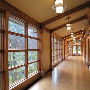 Idéer för en stor amerikansk hall, med bruna väggar, ljust trägolv och brunt golv