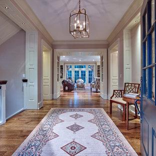 Réalisation d'un grand couloir tradition avec un mur rose et un sol en bois brun.
