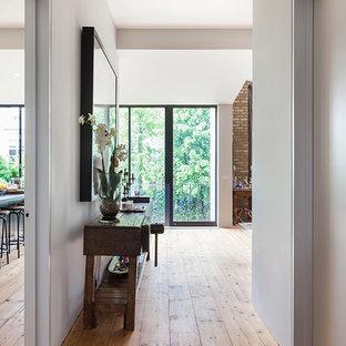 Идея дизайна: маленький коридор в современном стиле с белыми стенами, полом из ламината и коричневым полом