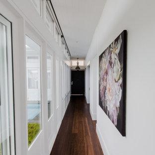 パースの広いサンタフェスタイルのおしゃれな廊下 (白い壁、無垢フローリング、茶色い床、塗装板張りの天井) の写真