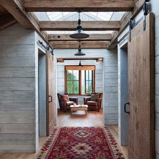 Bild på en rustik hall, med grå väggar, ljust trägolv och beiget golv