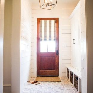 Cette photo montre un couloir chic de taille moyenne avec un mur blanc, un sol en brique et un sol multicolore.