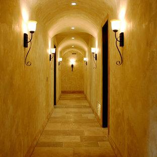 Неиссякаемый источник вдохновения для домашнего уюта: огромный коридор в средиземноморском стиле с бежевыми стенами, полом из известняка и бежевым полом
