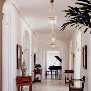 Cette photo montre un grand couloir chic avec un mur blanc, un sol en marbre et un sol beige.