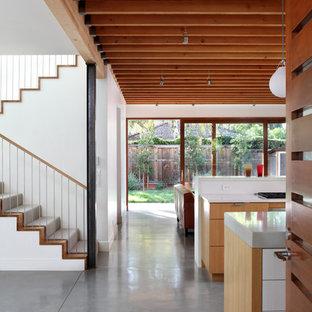 Idée de décoration pour un couloir design avec béton au sol et un sol gris.
