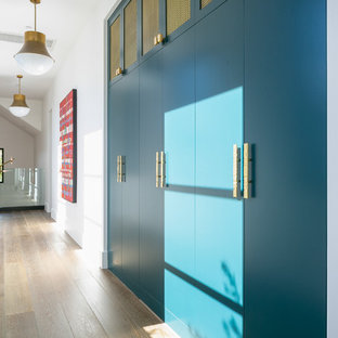 This is an example of a large hallway in Orange County with white walls, medium hardwood floors and brown floor.