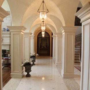 Cette image montre un grand couloir méditerranéen en bois avec un mur beige, un sol en marbre, un sol blanc et un plafond voûté.