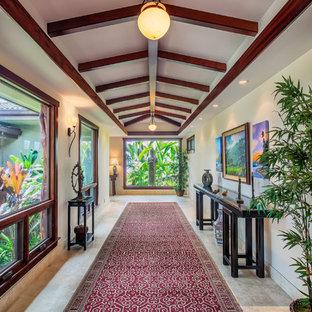ハワイの巨大なトロピカルスタイルのおしゃれな廊下 (トラバーチンの床、白い壁、グレーの床) の写真