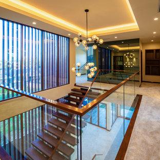 Стильный дизайн: огромный коридор в современном стиле с бежевыми стенами, ковровым покрытием, бежевым полом и многоуровневым потолком - последний тренд