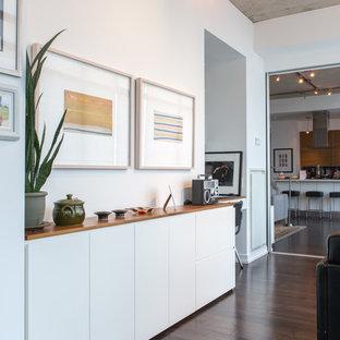 Modern inredning av en liten hall, med vita väggar, mörkt trägolv och brunt golv