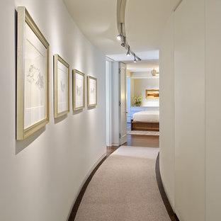 Inspiration pour un couloir design de taille moyenne avec un mur beige et moquette.