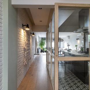 Cette photo montre un couloir tendance de taille moyenne avec un mur blanc, un sol en bois clair, un sol beige et un mur en parement de brique.