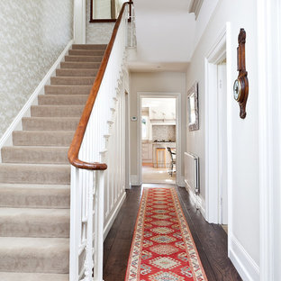 Cette image montre un couloir victorien avec un mur blanc, un sol en bois foncé et un sol marron.