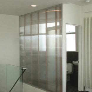 Foto de recibidores y pasillos modernos con paredes blancas y suelo de madera oscura