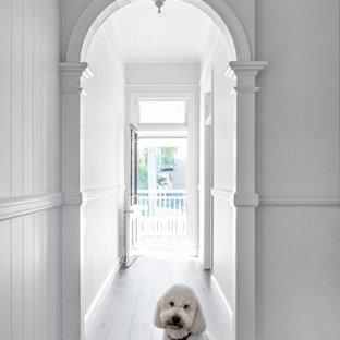 Foto på en stor vintage hall, med vita väggar, mörkt trägolv och brunt golv
