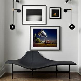 Foto på en funkis hall, med vita väggar och mörkt trägolv