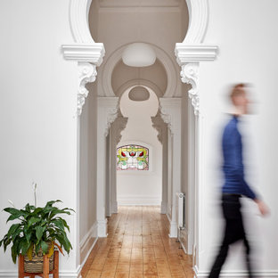 This is an example of a contemporary hallway in Melbourne with white walls, medium hardwood floors and brown floor.