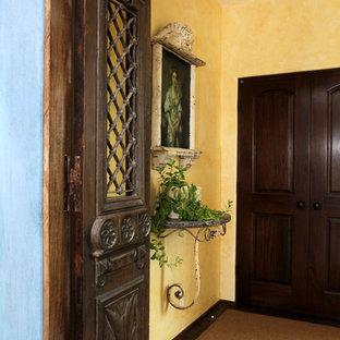 Immagine di un piccolo ingresso o corridoio mediterraneo con pareti gialle, moquette e pavimento marrone