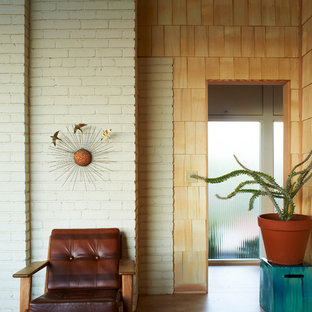 This is an example of a mid-sized midcentury hallway in New York with white walls, porcelain floors and beige floor.