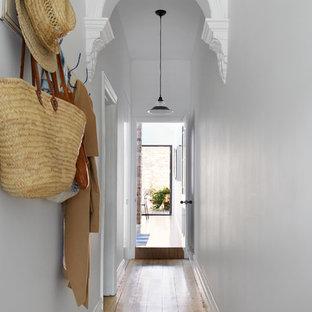 Ejemplo de recibidores y pasillos clásicos con paredes grises y suelo de madera clara
