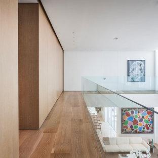 Exempel på en modern hall, med vita väggar, mellanmörkt trägolv och brunt golv
