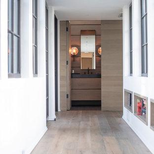 Стильный дизайн: большой коридор в стиле неоклассика (современная классика) с белыми стенами, светлым паркетным полом, серым полом и деревянными стенами - последний тренд
