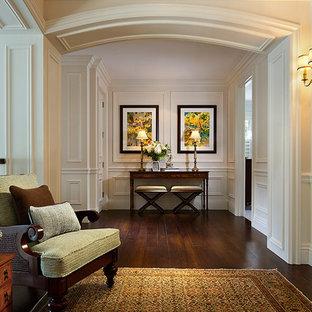 Ejemplo de recibidores y pasillos tradicionales, grandes, con suelo de madera oscura, paredes beige y suelo marrón