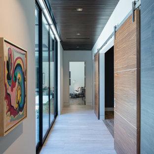 Cette photo montre un grand couloir tendance avec un mur blanc, un sol en carrelage de porcelaine, un sol beige et un plafond en bois.