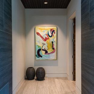 Cette photo montre un couloir tendance de taille moyenne avec un mur blanc, un sol en carrelage de porcelaine, un sol beige et un plafond en bois.