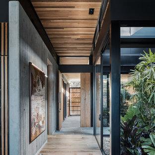 Aménagement d'un couloir industriel avec un mur gris et un sol en bois brun.