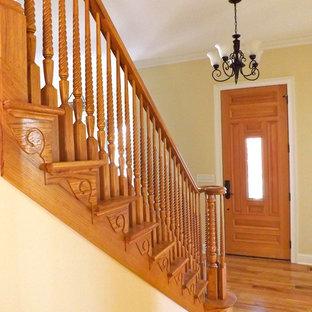 Idées déco pour un couloir éclectique de taille moyenne avec un mur jaune et un sol en bois brun.