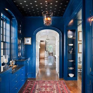 Diseño de recibidores y pasillos clásicos con paredes azules y suelo de madera oscura