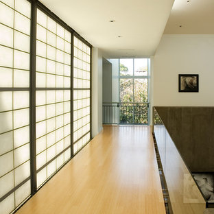 Exempel på en modern hall, med vita väggar, ljust trägolv och gult golv