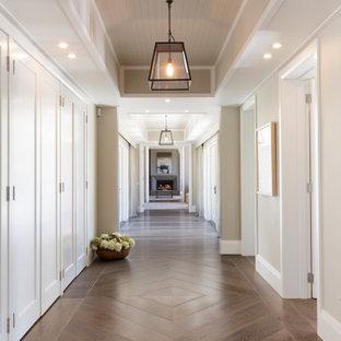 На фото: большой коридор в стиле кантри с паркетным полом среднего тона, коричневым полом и кессонным потолком