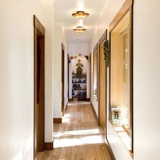 Ispirazione per un ingresso o corridoio etnico con pareti bianche, pavimento in legno massello medio e pavimento marrone