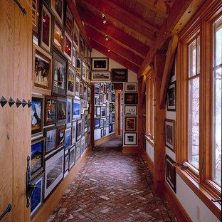 Idéer för en lantlig hall, med vita väggar och tegelgolv