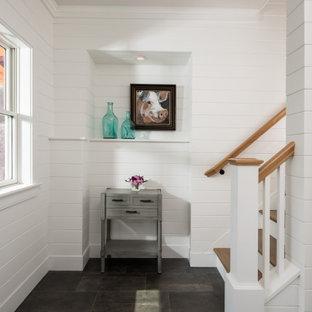 Cette image montre un couloir traditionnel de taille moyenne avec un mur blanc, un sol en carrelage de porcelaine, un sol noir et du lambris de bois.