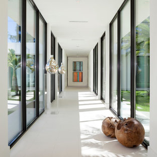 Example of a huge trendy porcelain floor and white floor hallway design in Miami with white walls
