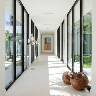 Inspiration pour un très grand couloir design avec un mur blanc, un sol en carrelage de porcelaine et un sol blanc.