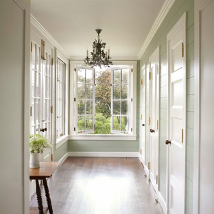 This is an example of a large beach style hallway in Boston with green walls and dark hardwood floors.