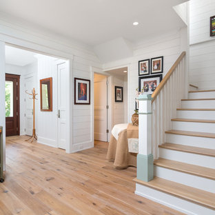 Photo of a mid-sized beach style hallway in Atlanta with white walls and medium hardwood floors.