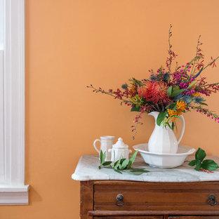 Idées déco pour un petit couloir campagne avec un mur orange et un sol en bois brun.