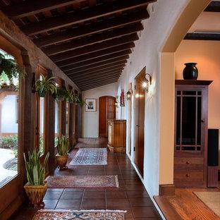 Hallway - mediterranean terra-cotta tile hallway idea in San Diego with white walls
